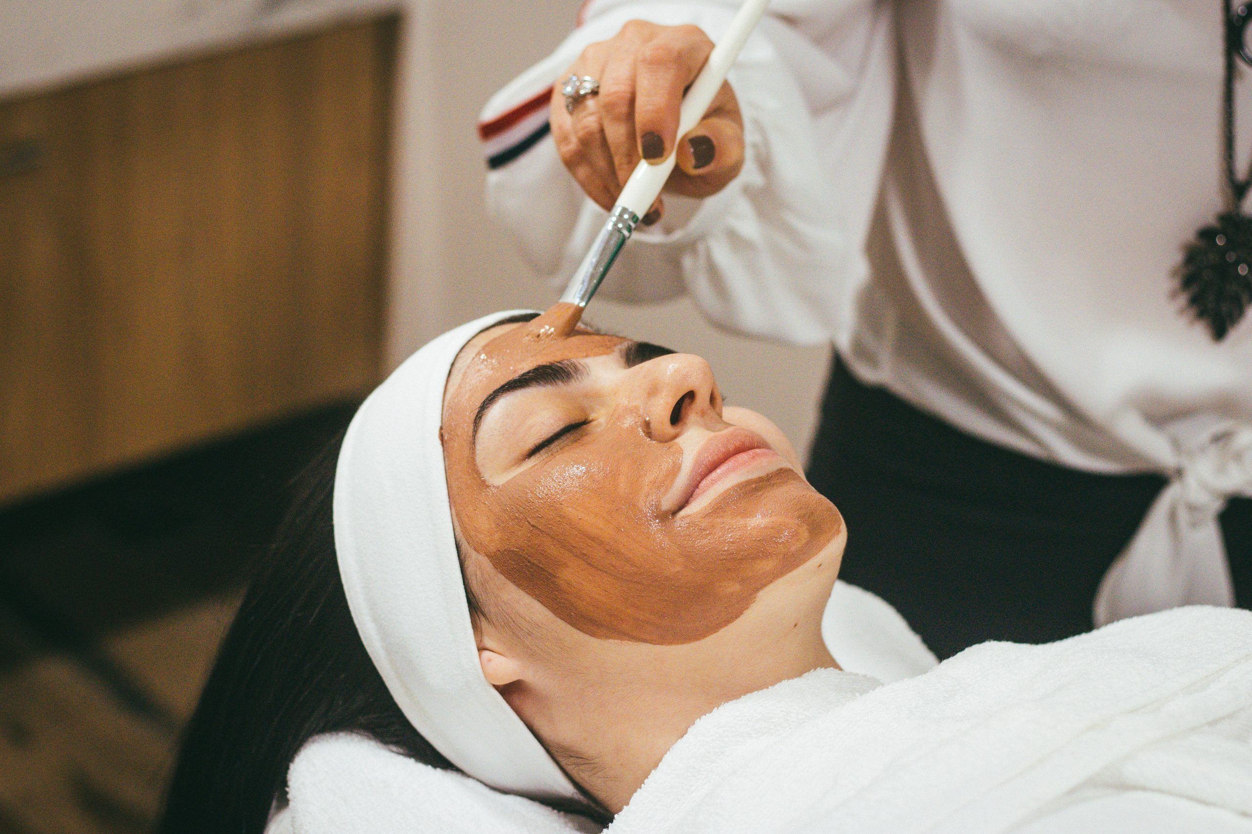 woman lying down, eyes closed, mid facial treatment for glowing skin