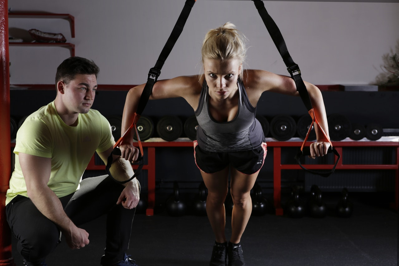 Personal Trainer Crouched Beside Person Working On Fitness Levels, Success Tips