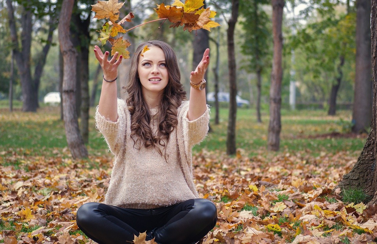 Person Sitting Outside Among Fallen Autumn Leaves Throws A Bundle Of Leaves In The Air, Unwind This Autumn