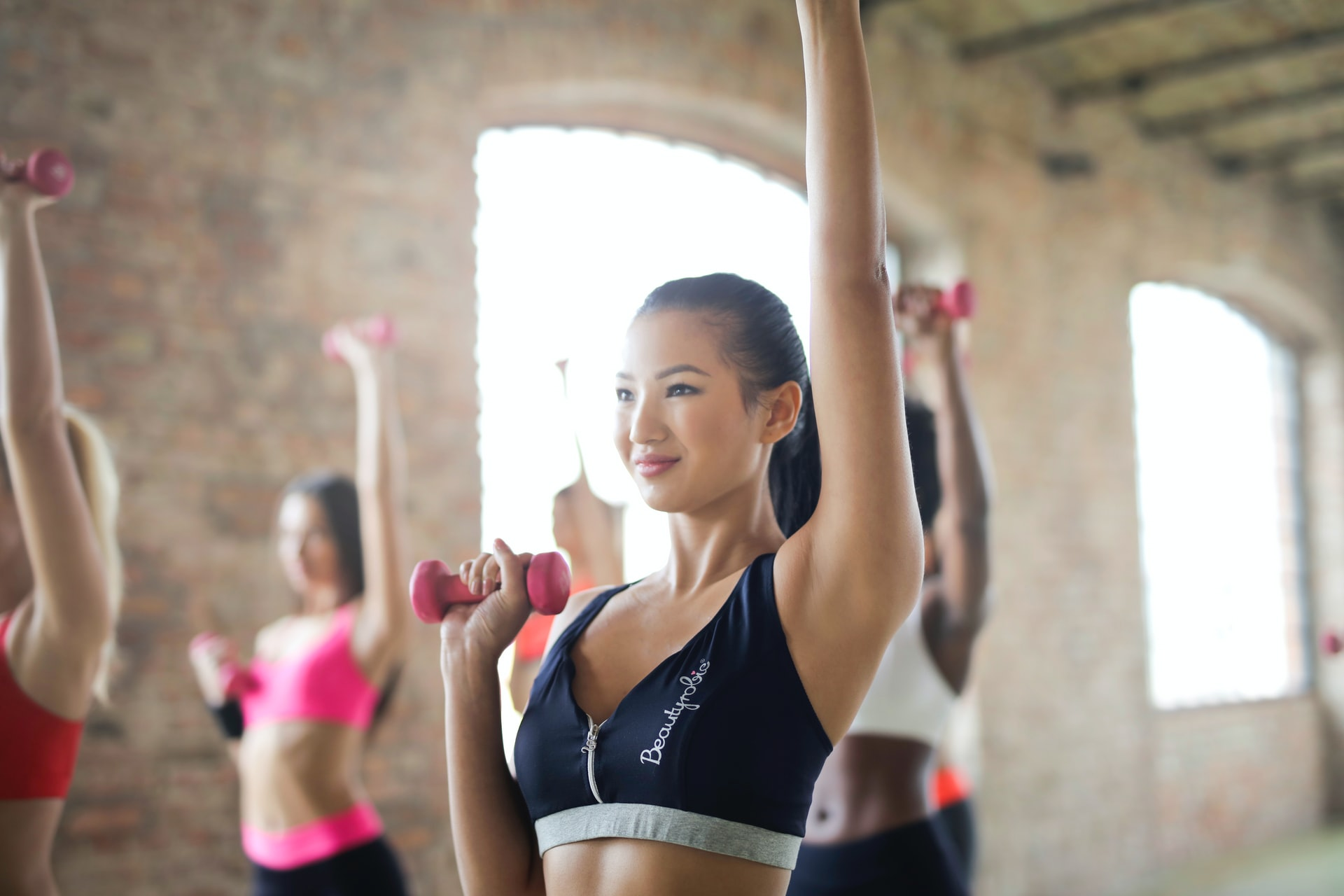 Group Of People Exercising With Dumbbells