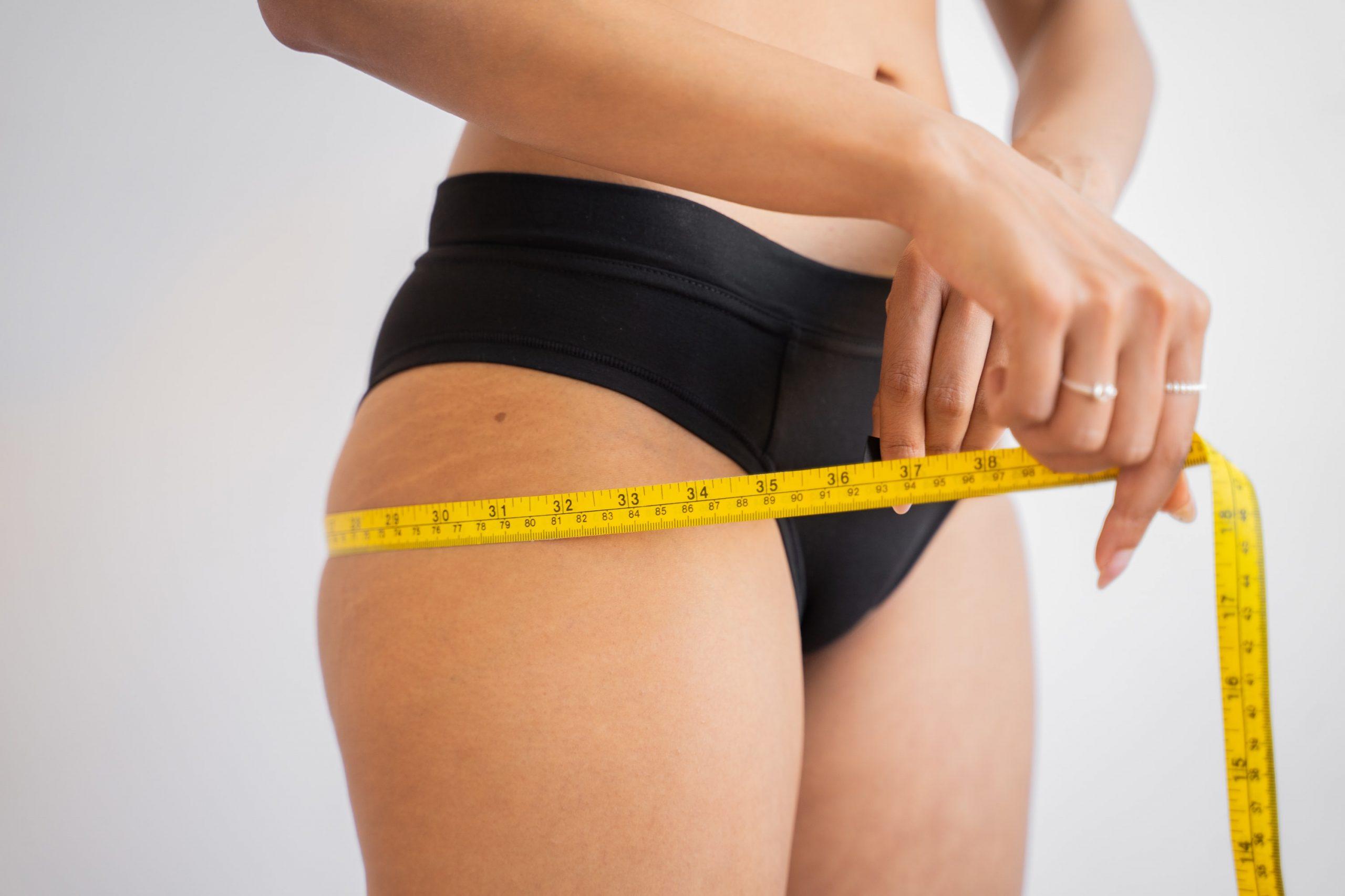 Woman in underwear using measuring tape