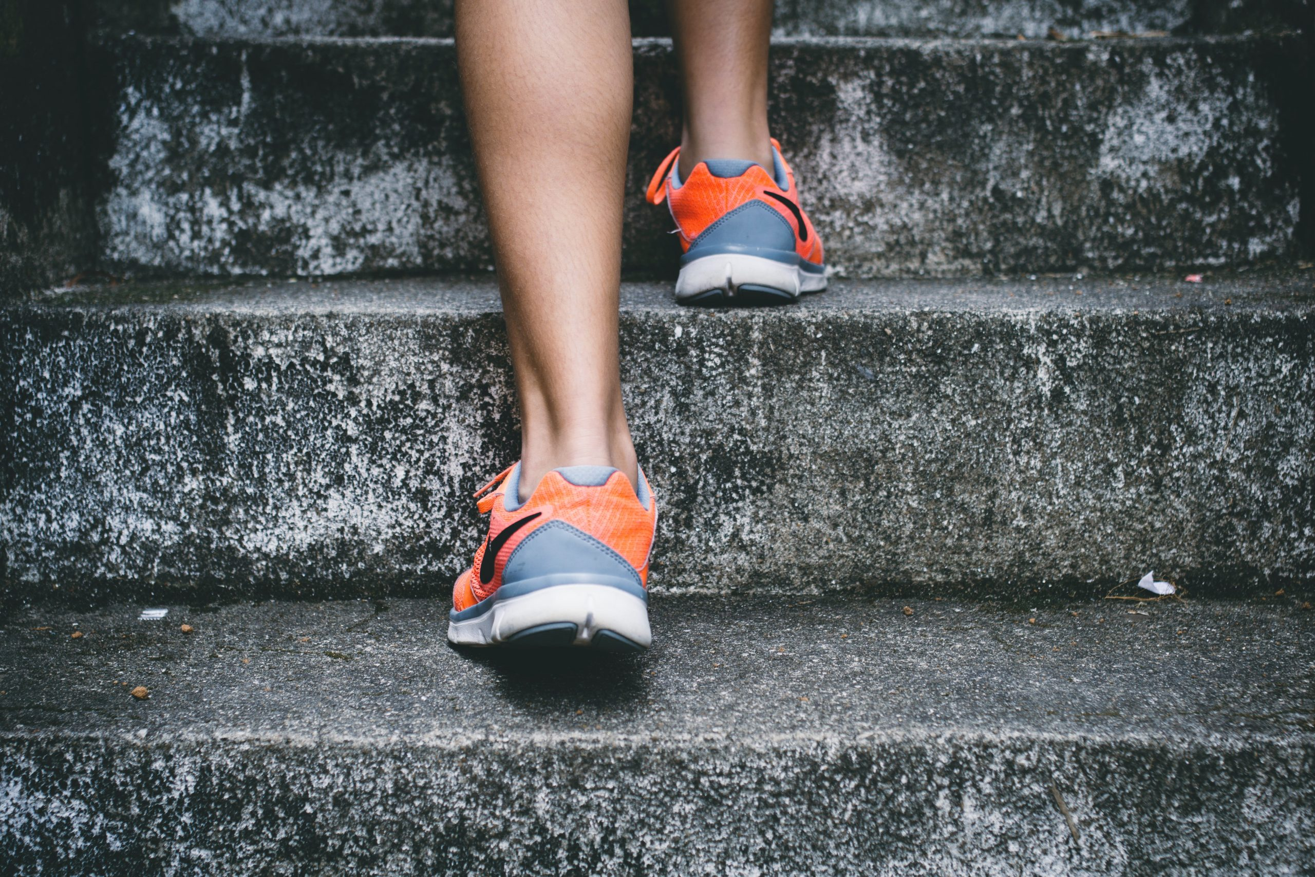 Person's feet in trainers, bare legs, ascending stairs
