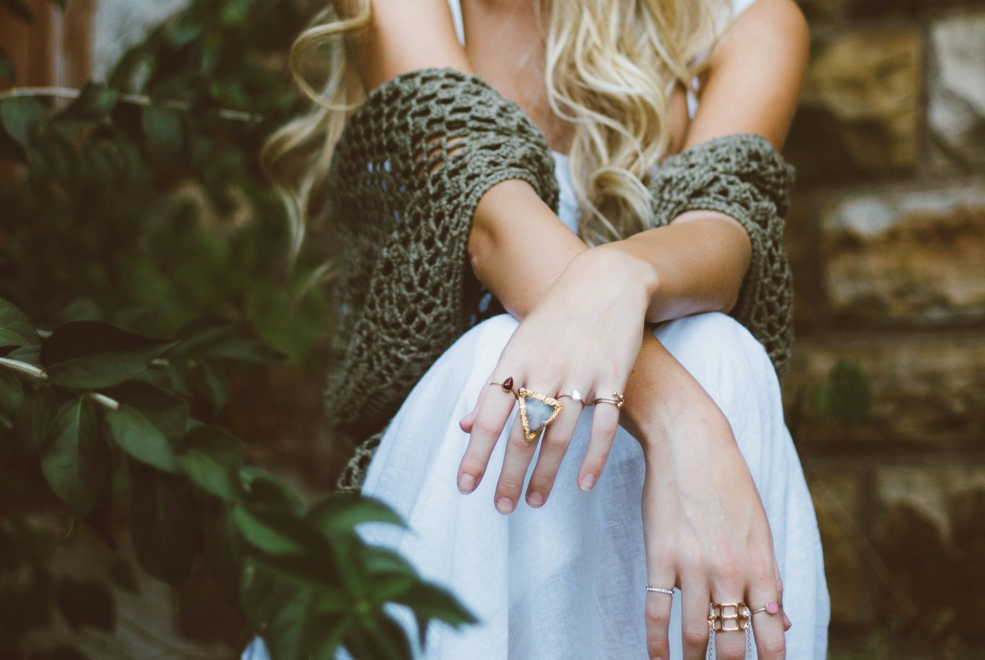 Closeup Of Person's Hands Crossed Over Knees, Wearing Rings, Youthful, Sitting Beside Plants, Anti-ageing For Hands
