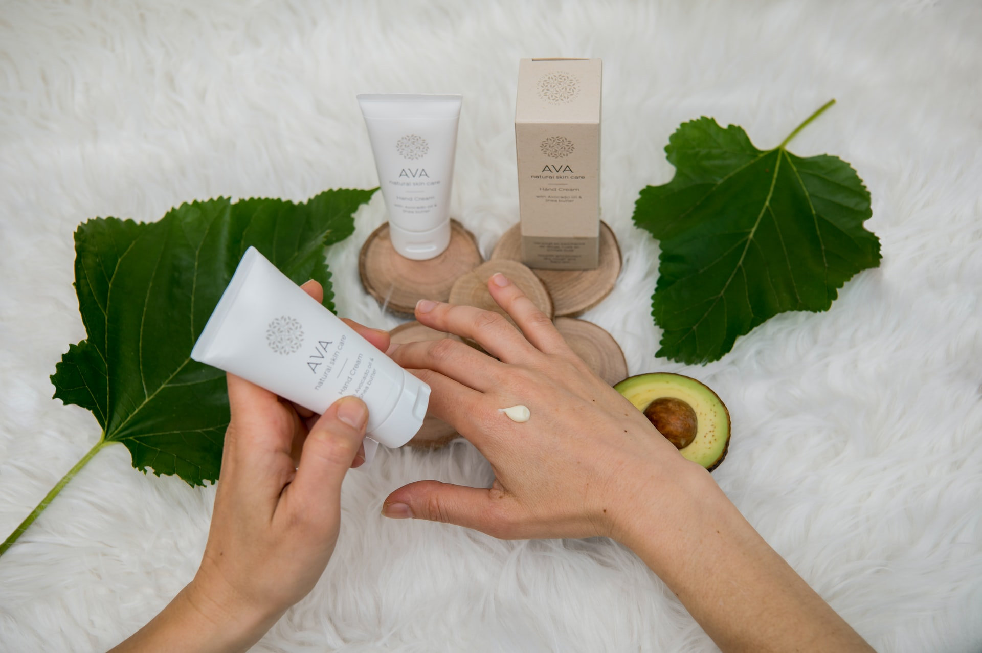 closeup of hands applying skincare product above a selection of skincare products