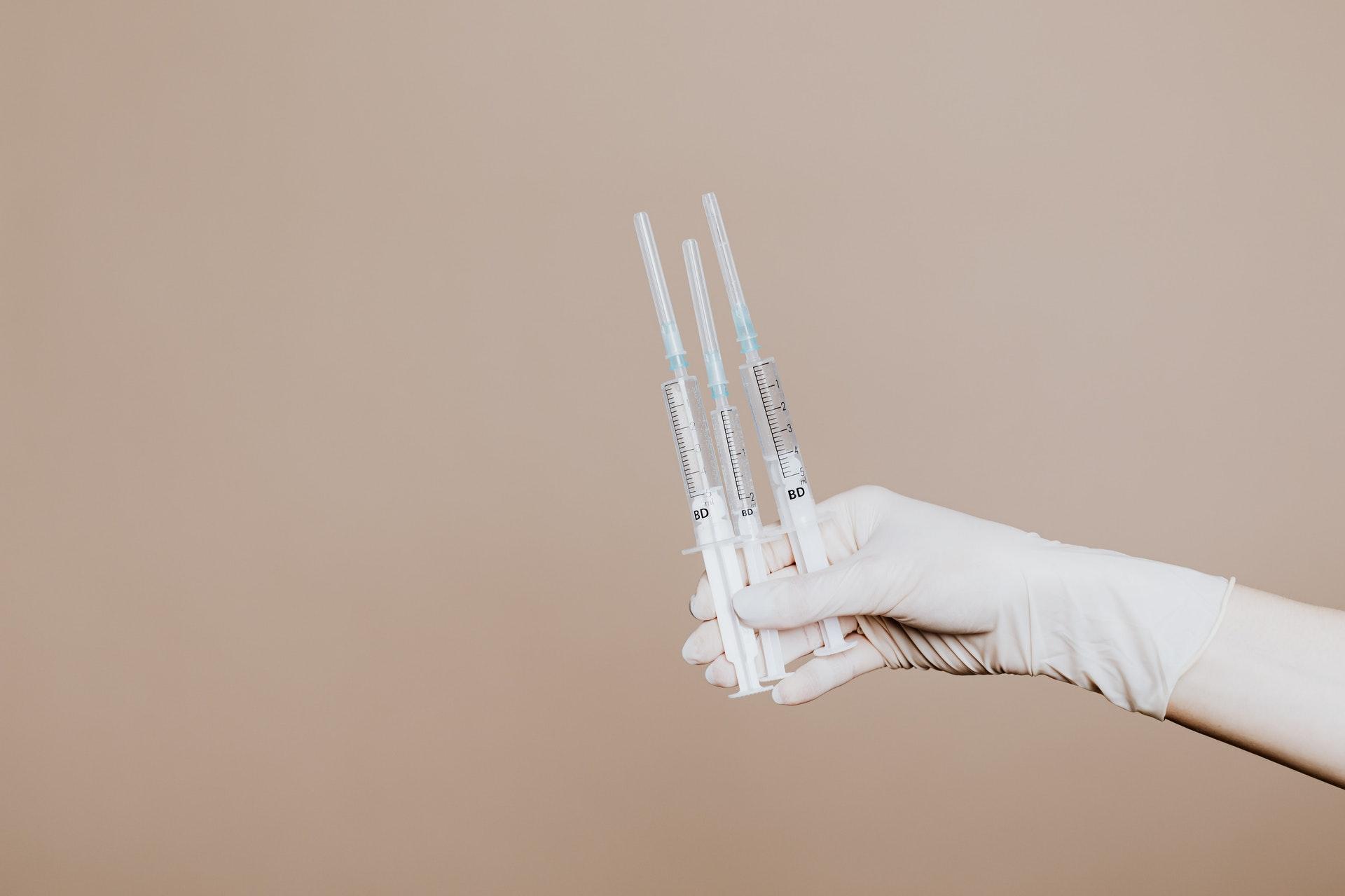 gloved hand holding hypodermic needles against plain backdrop