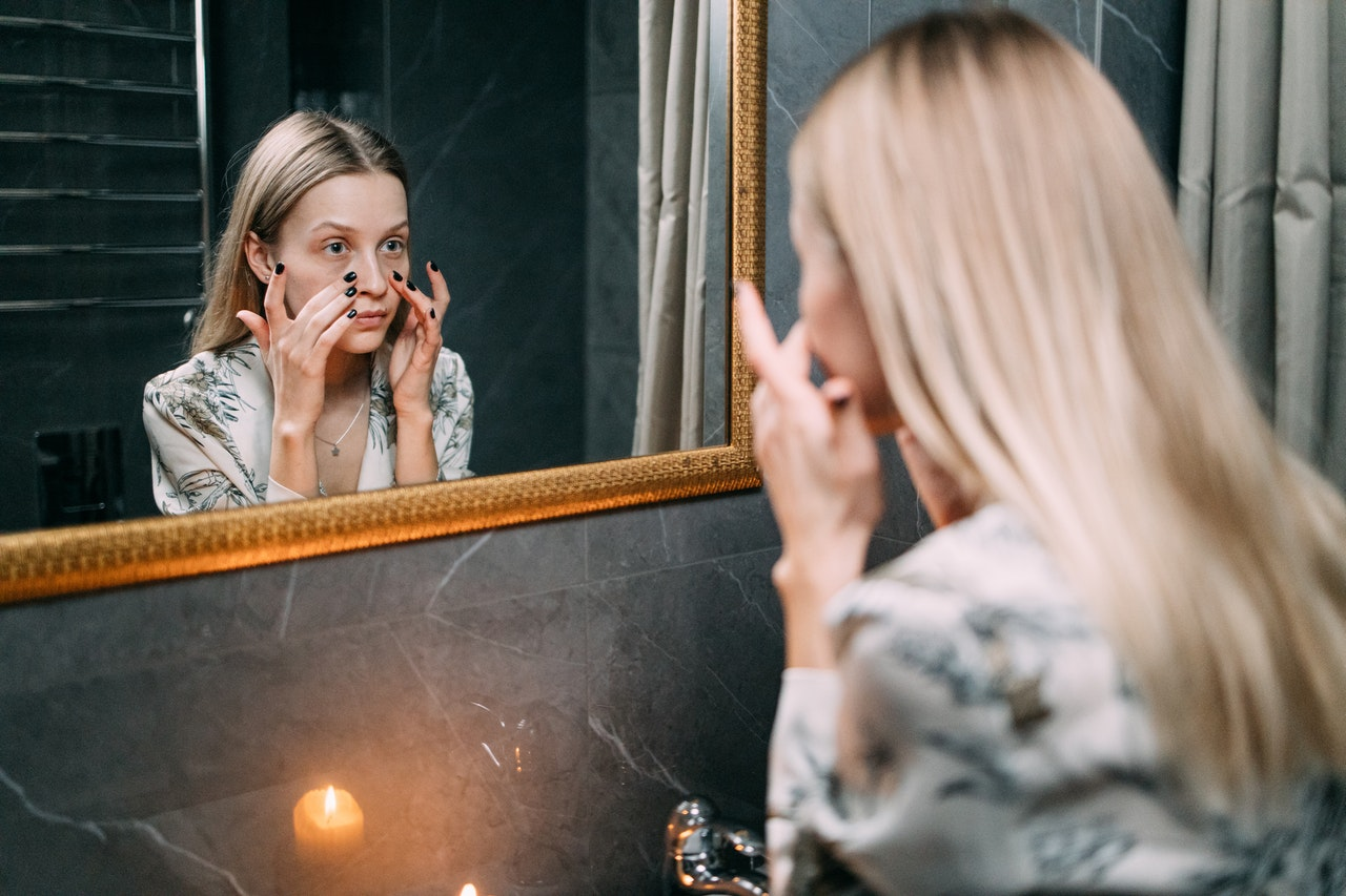 person looking in mirror and exfoliating, autumn skincare