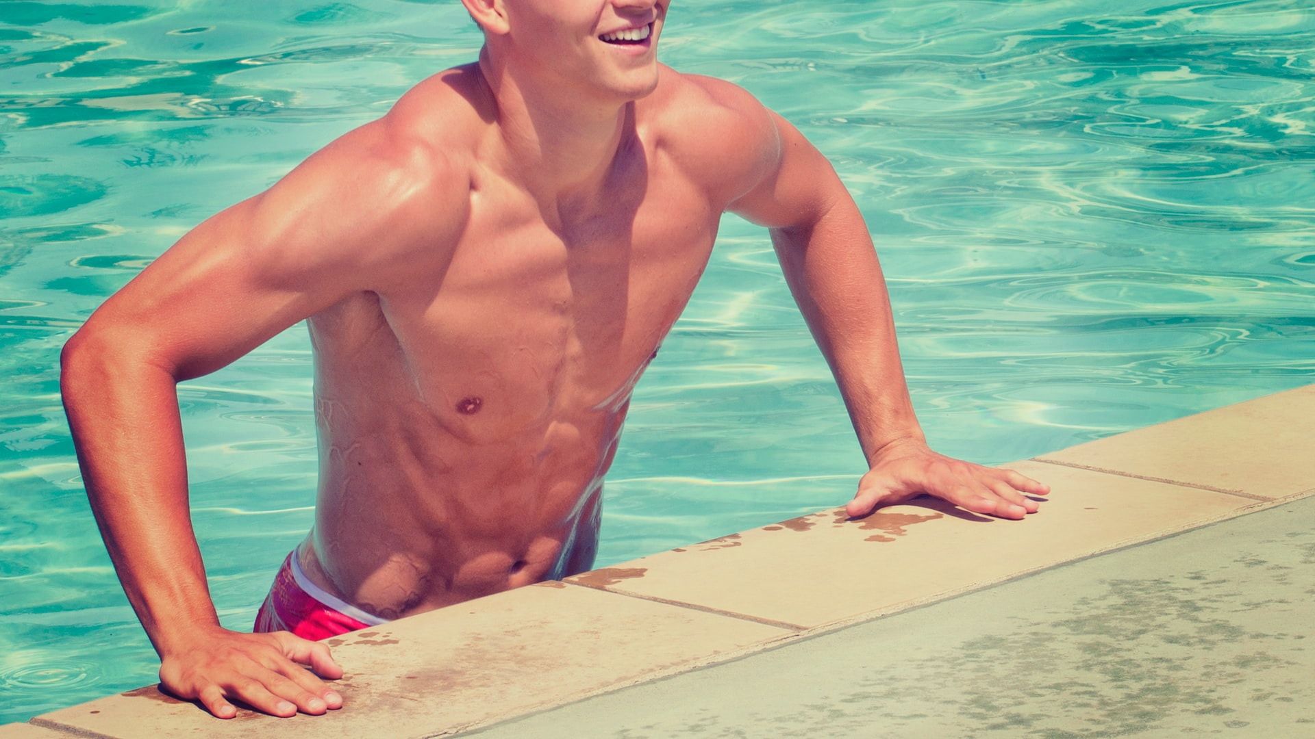 shirtless man with abs exiting pool