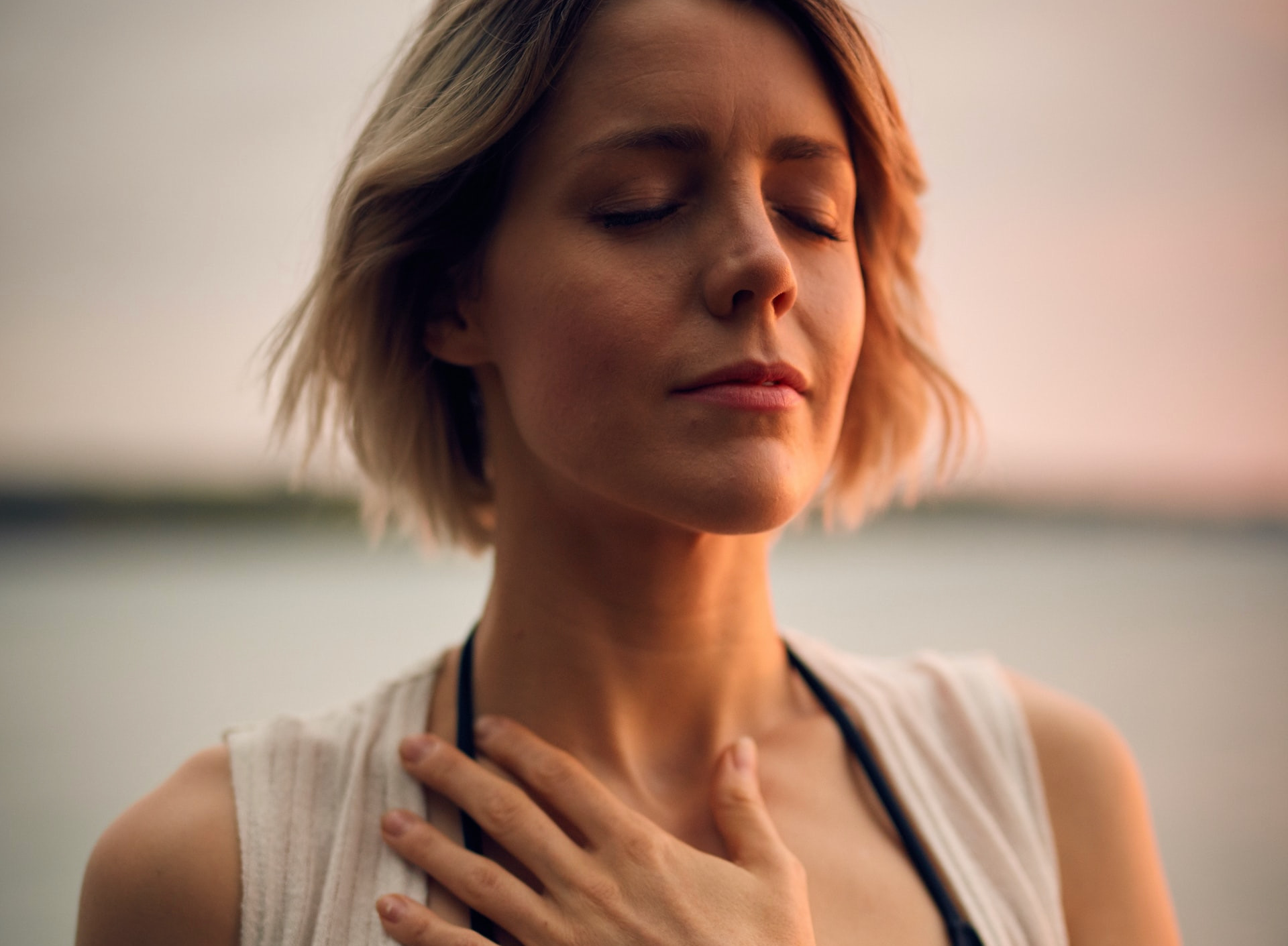 Person In Setting Sunlight, Eyes Closed, Hand On Chest