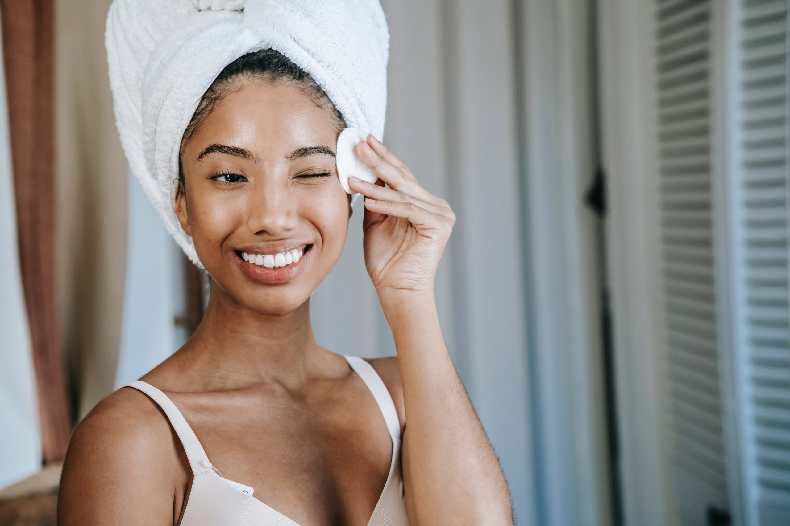 smiling woman cleansing her face