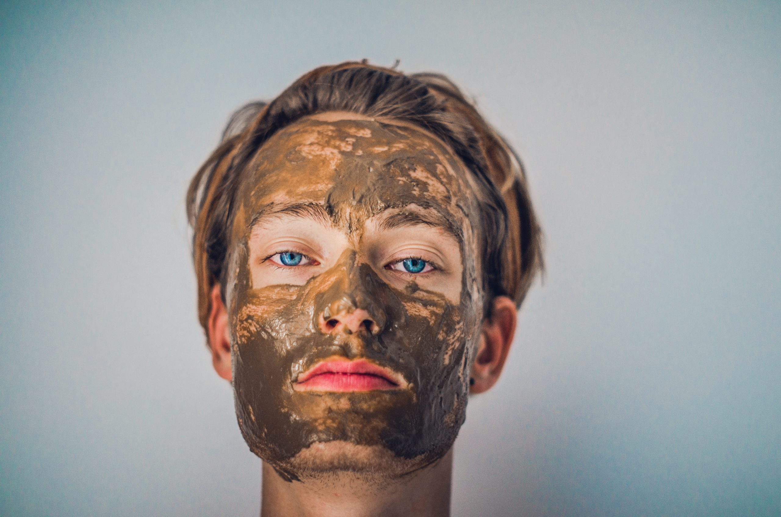 man wearing a clay mask, skincare