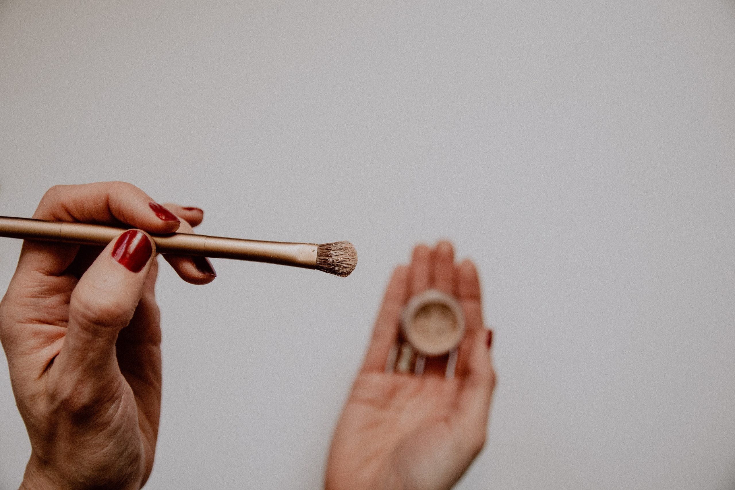 hands holding make-up pot and brush