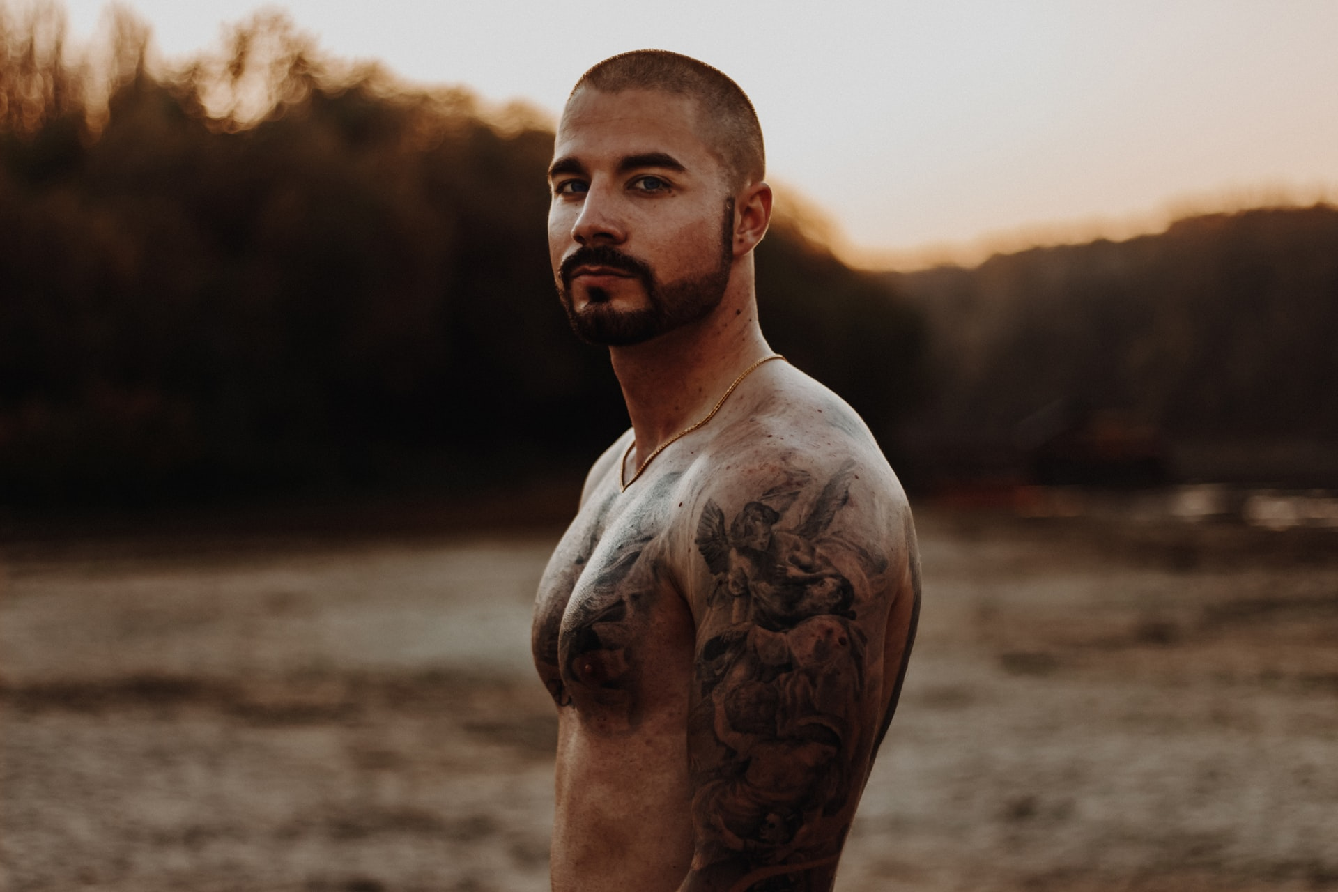topless man with defined pectoral muscles looks at camera