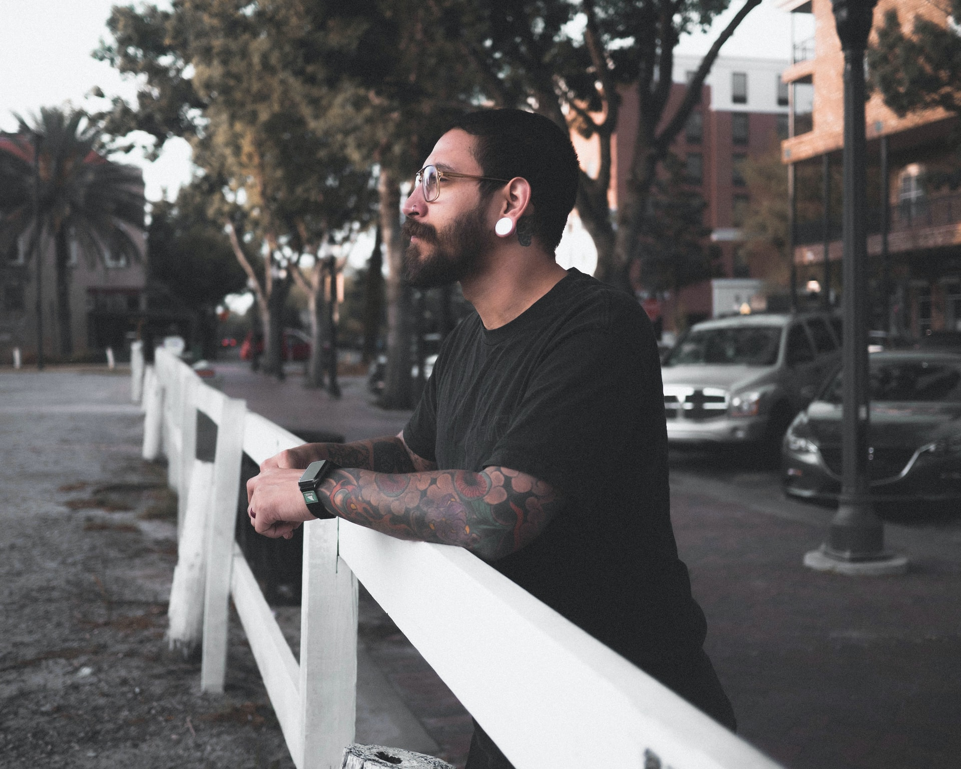 tattooed man with glasses and piercing leans on white rail during daytime