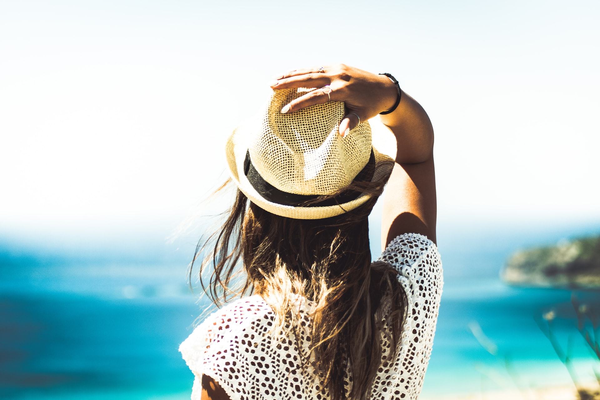 view of person from behind, hand on head, looking out to sea in the summer sun, does sun affect acne