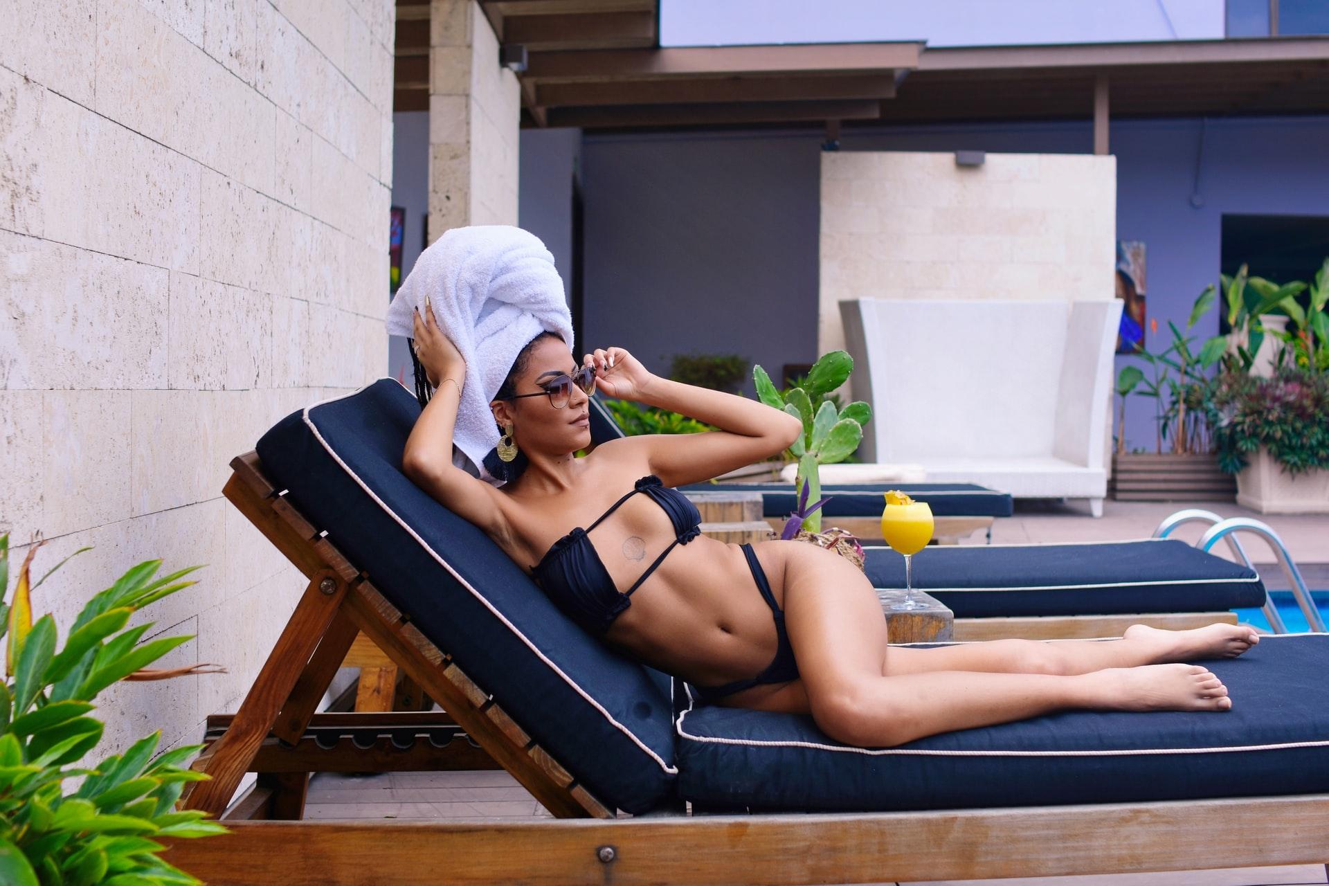 woman lying on sunlounge in bikini, towel on head, sunglasses on
