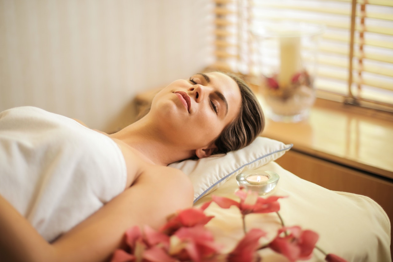 person lying down in relaxing setting, awaiting chemical peel skincare treatment