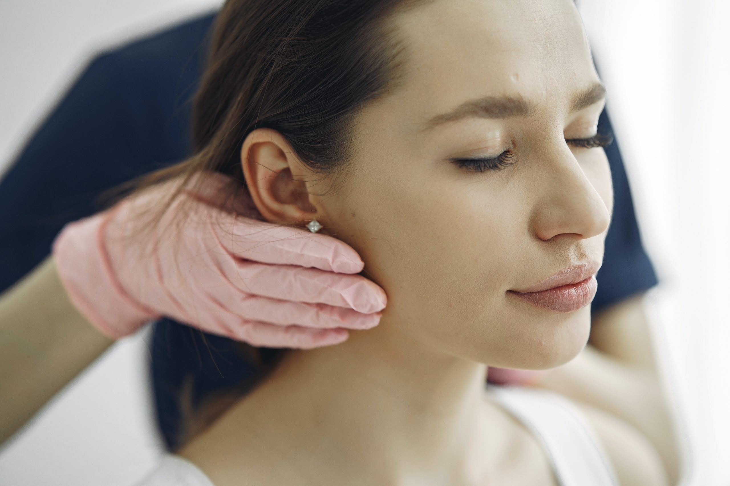 woman with eyes closed has her glands checked by professional