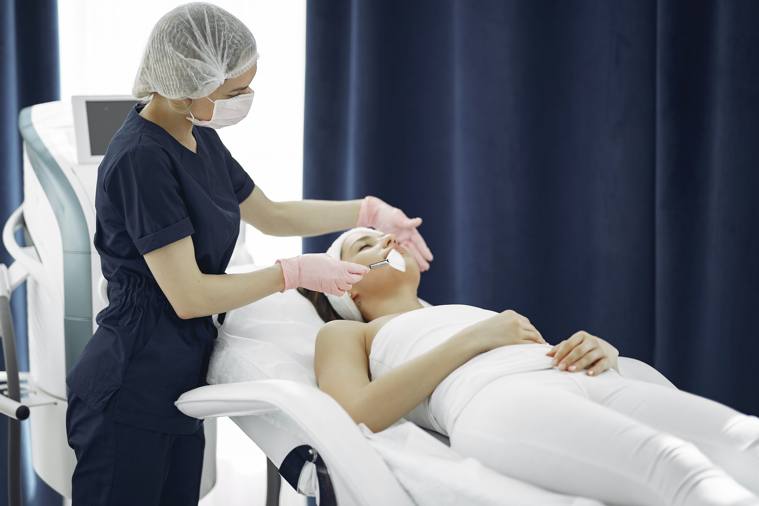 woman lying on surgical bed, mid-procedure, dermal fillers