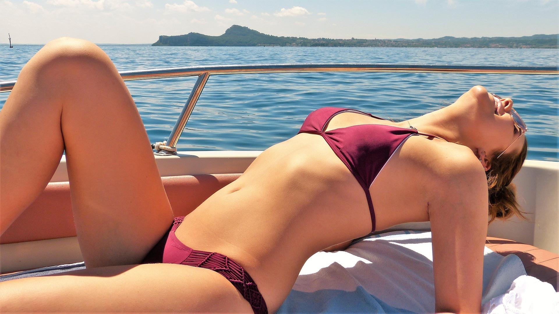 woman in bikini sunbathing on a boat