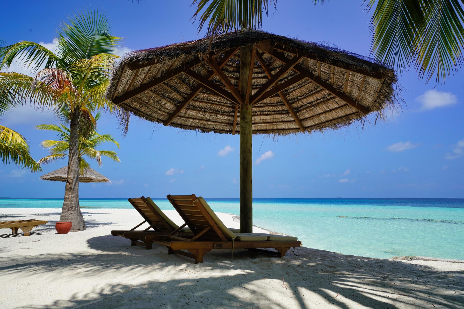 sunny tropical beach, tan beds under parasol