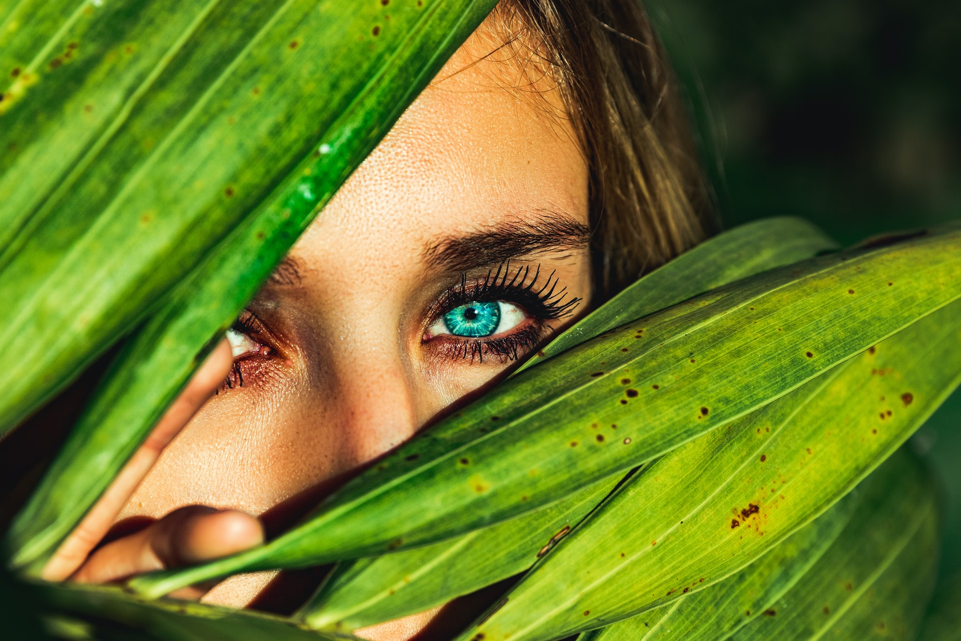closeup of person's eyes, hiding behind plant leaves, why you need eye cream