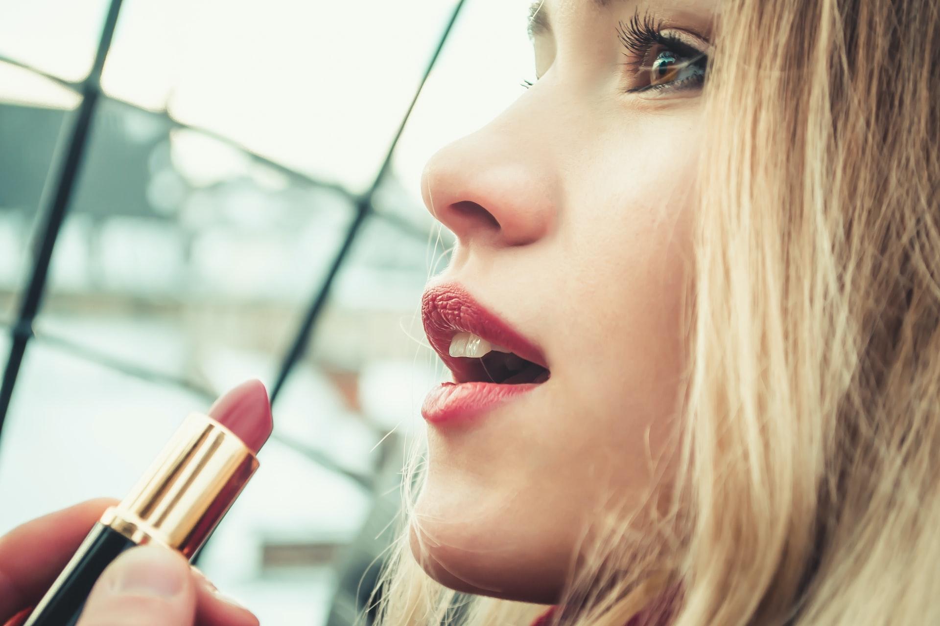 closeup of blonde woman applying lipstick