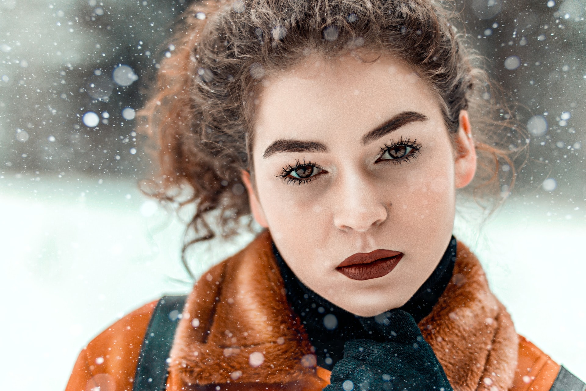 Person With Healthy Skin Looks At Camera, Snowy Background