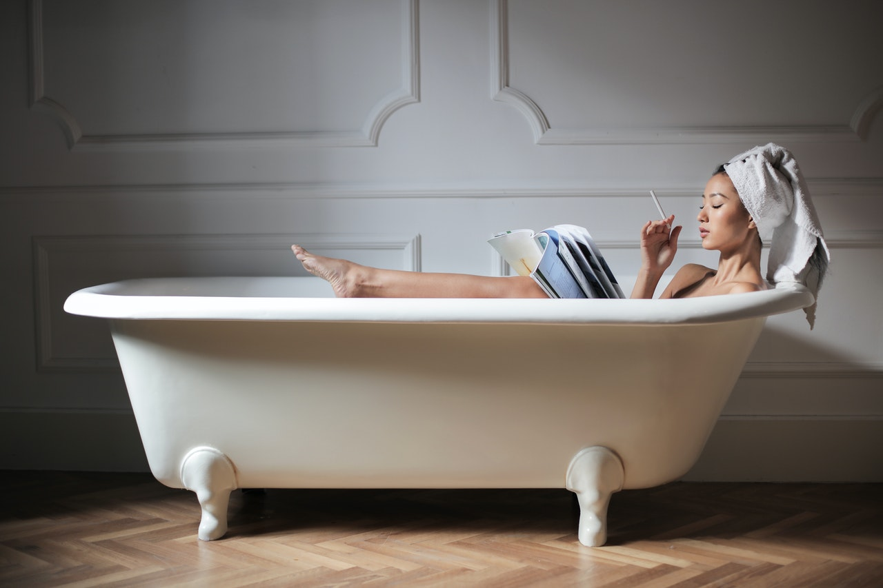 person in bathtub, towel on head, how to treat hard water issues