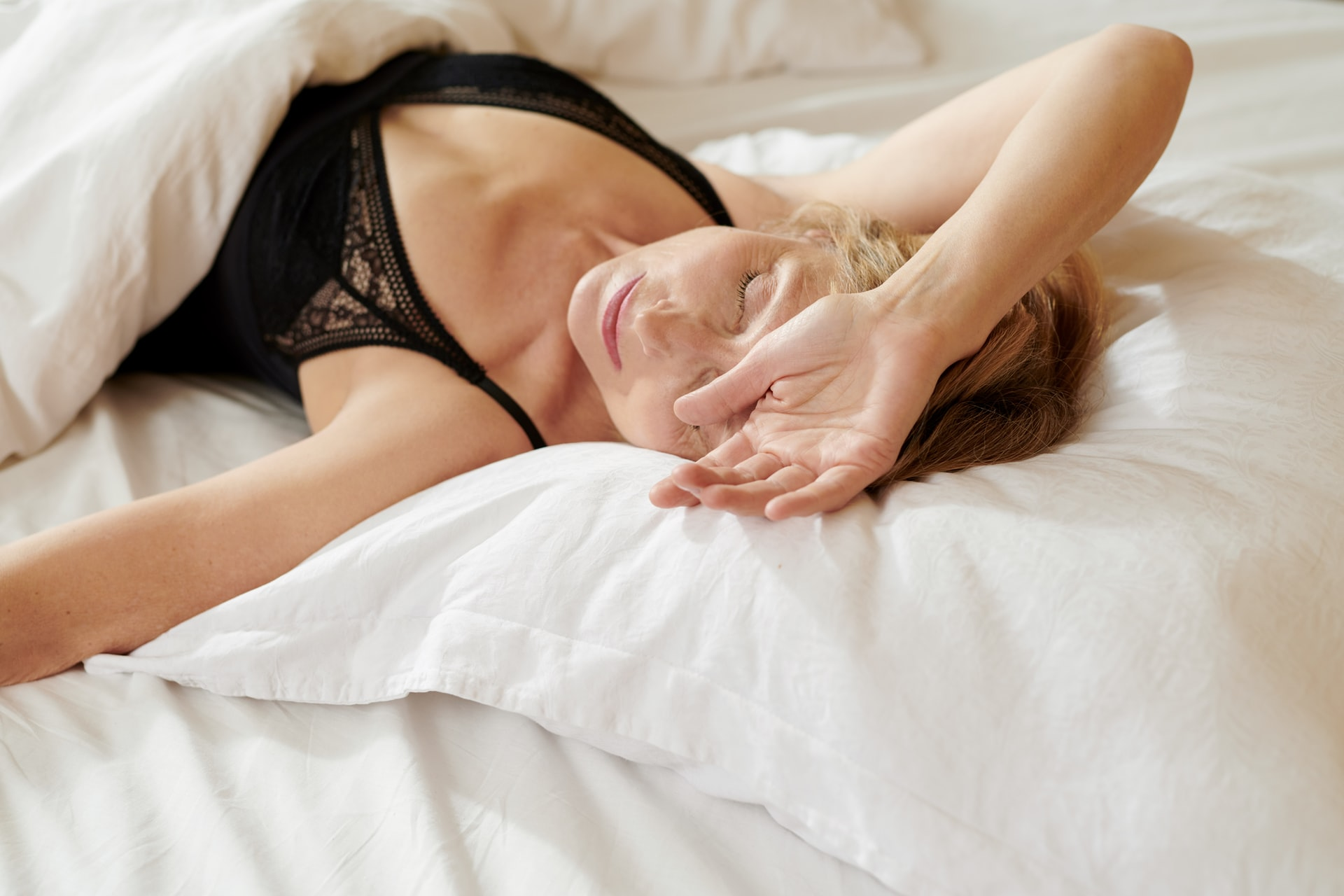 middle aged woman lying in bed, posed with arm on forehead, beauty