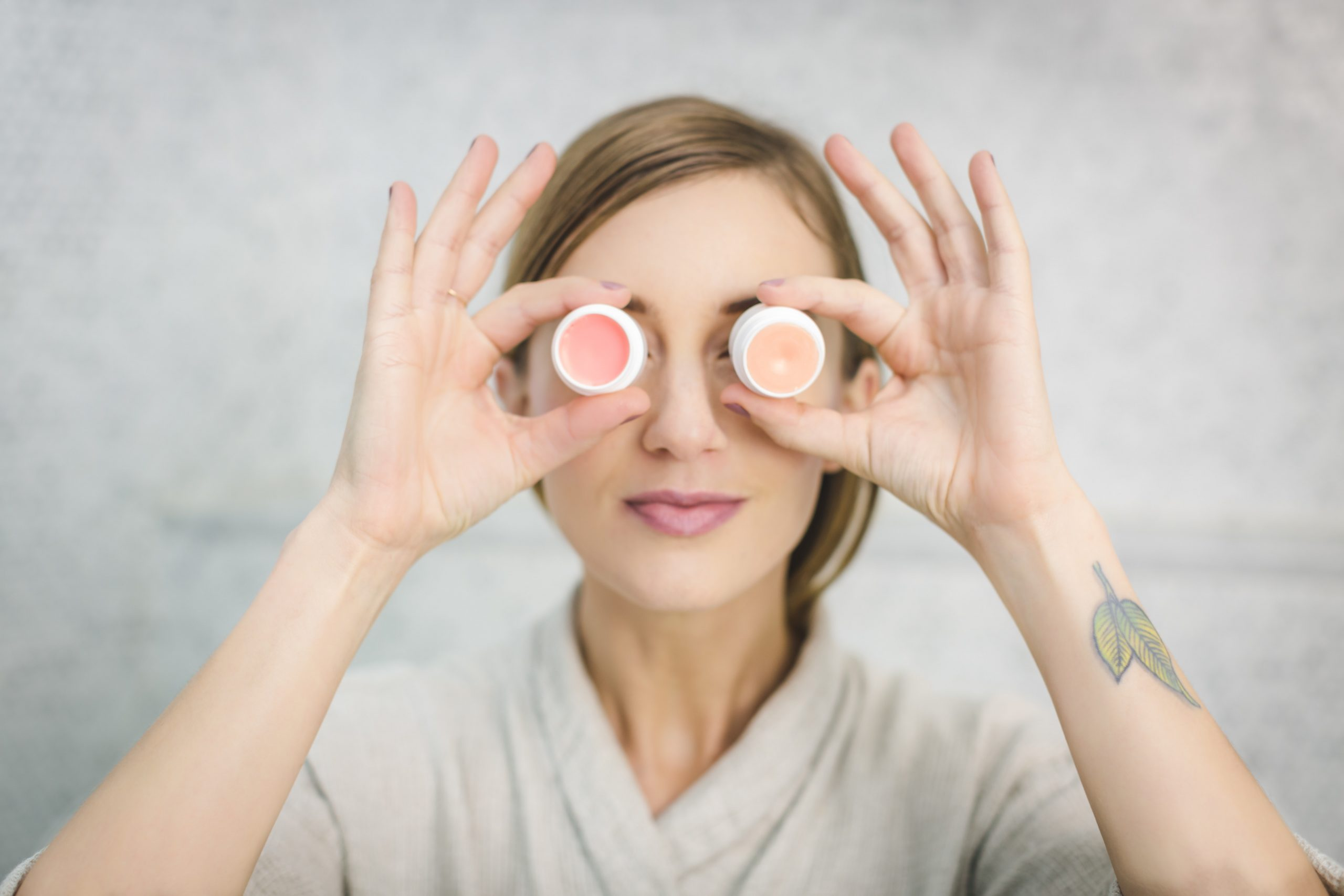 woman holding skincare products against her eyes