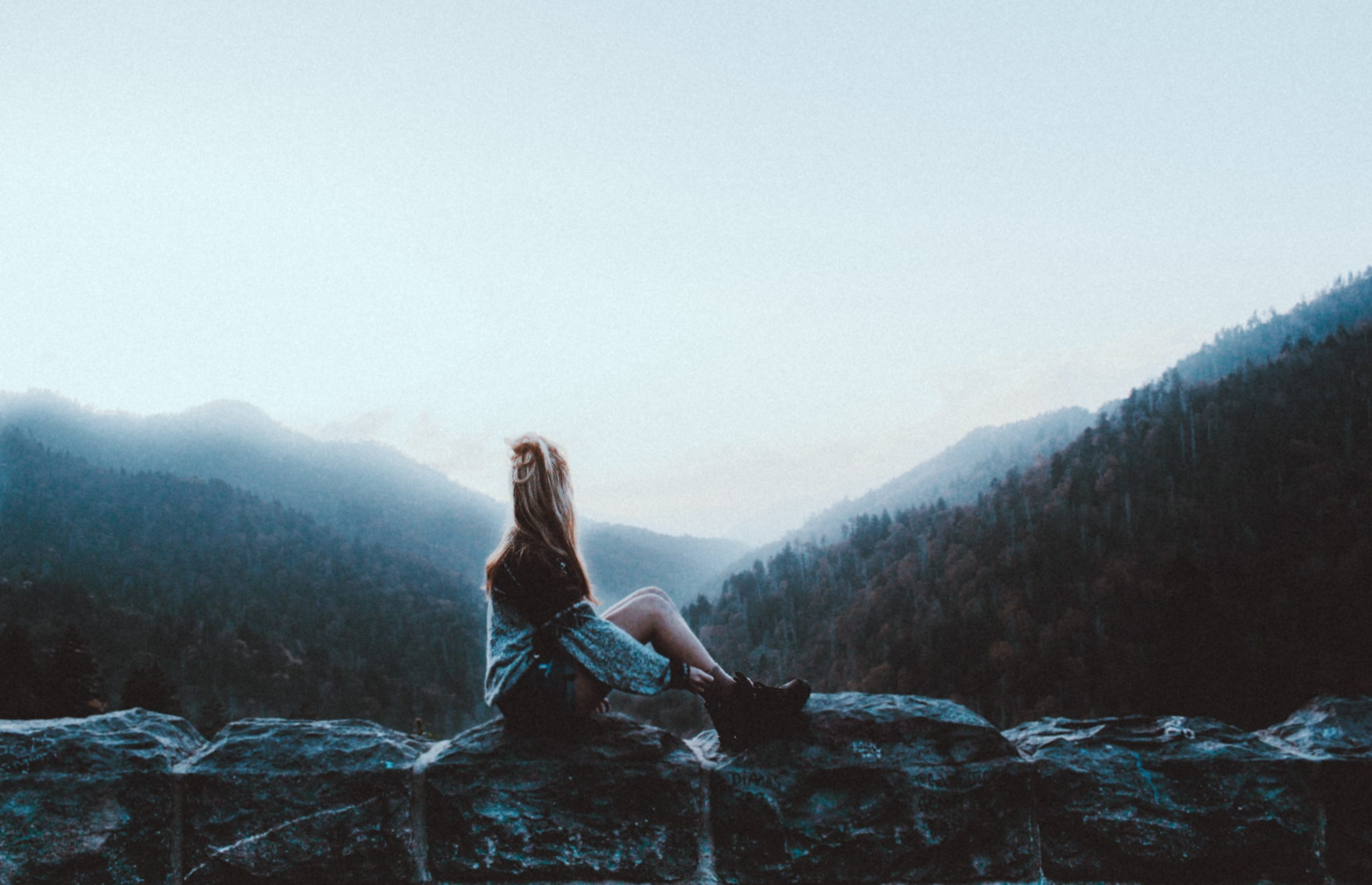 adventurous woman sits on wall looking at mist and mountains