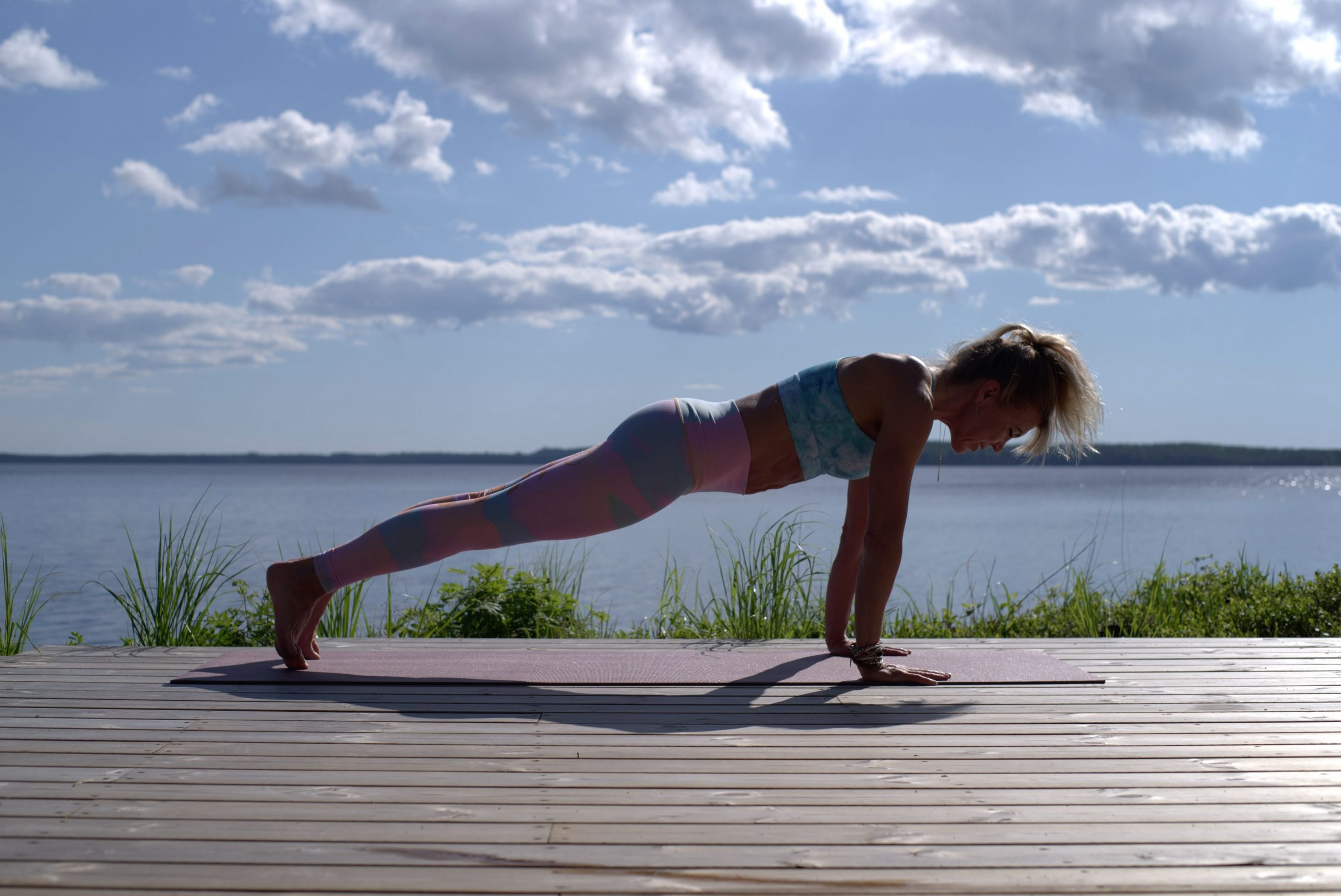 athletic woman in press-up position on boardwalk by lake