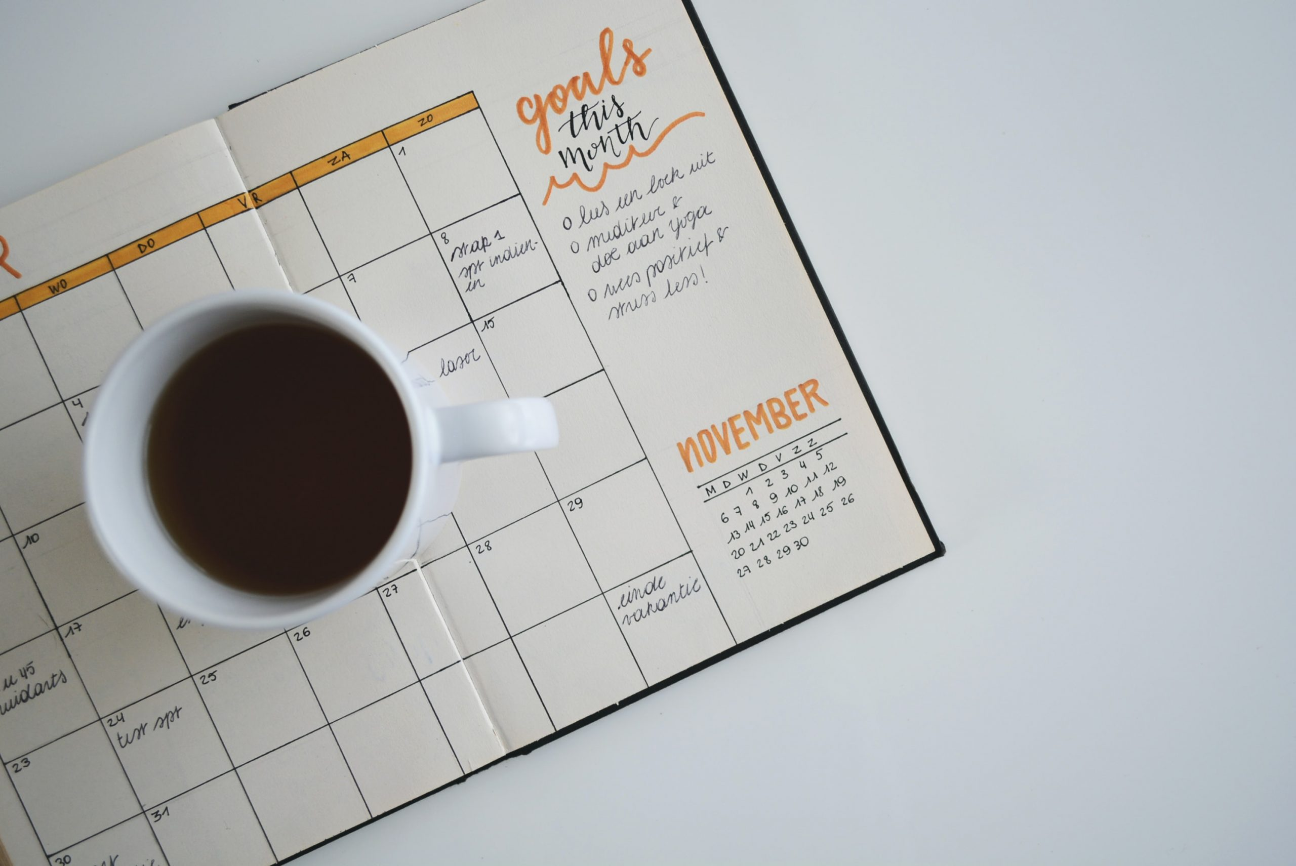 coffee cup resting on goal planner