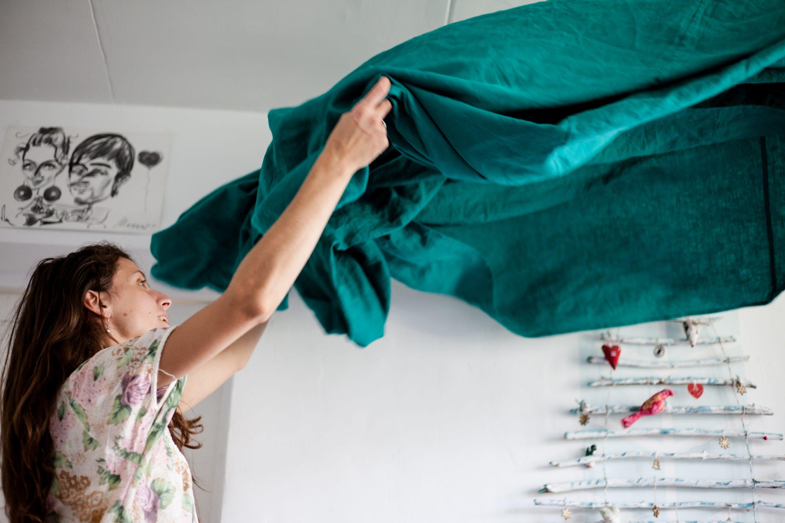 woman tidying sheets at home