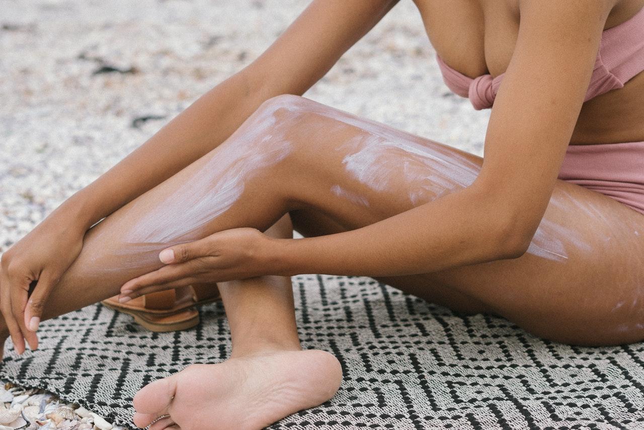 closeup of person's legs, applying SPF, summer skincare advice