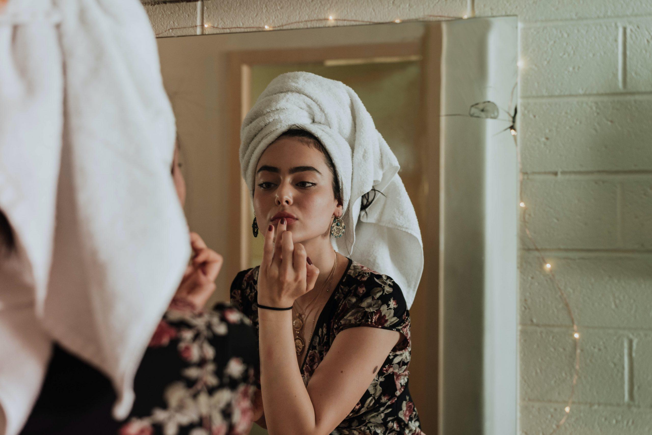 woman wearing towel on head looking in mirror, beauty