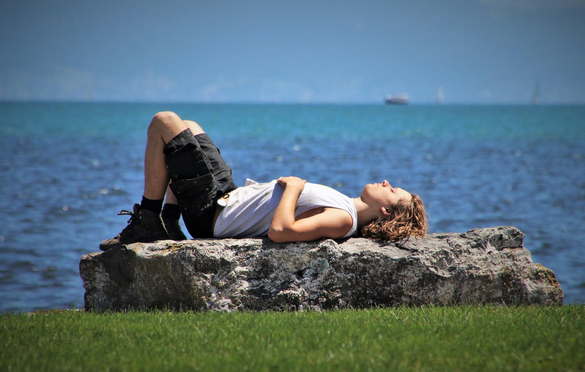man sunbathing on a rock by water