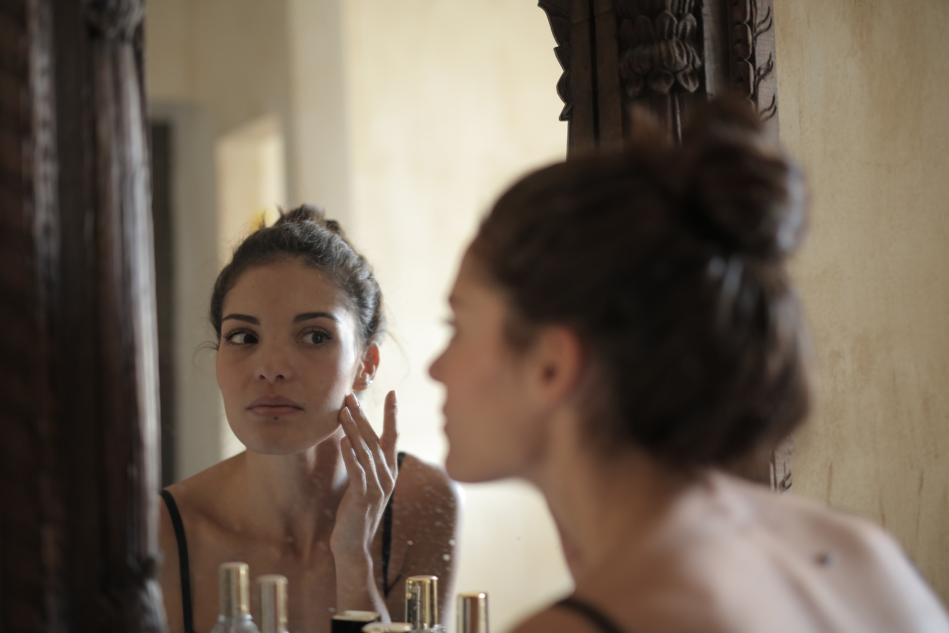 woman touching her cheek, looking in the mirror
