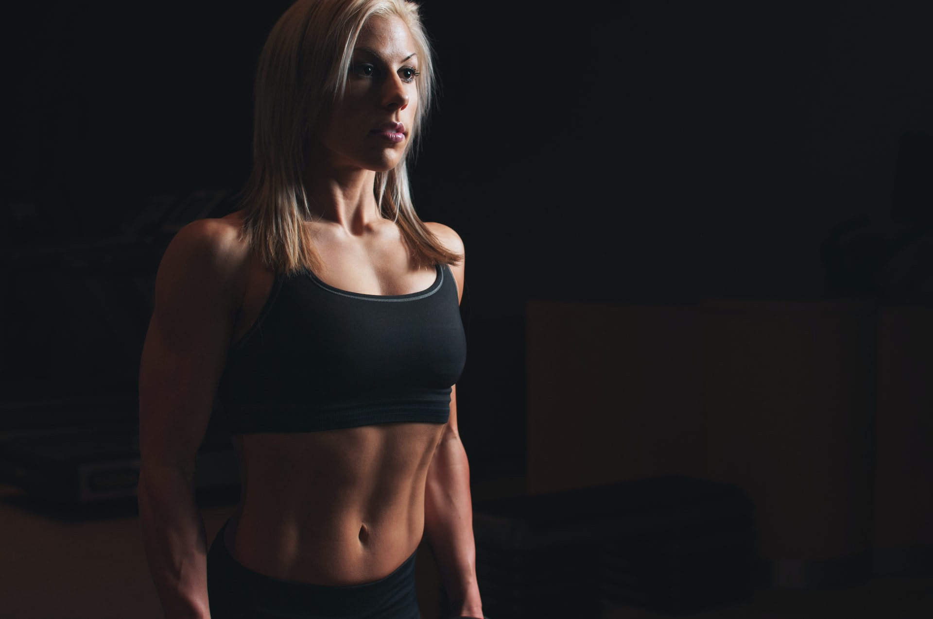toned person facing off-camera against black background, looking ready for fitness, coolsculpting