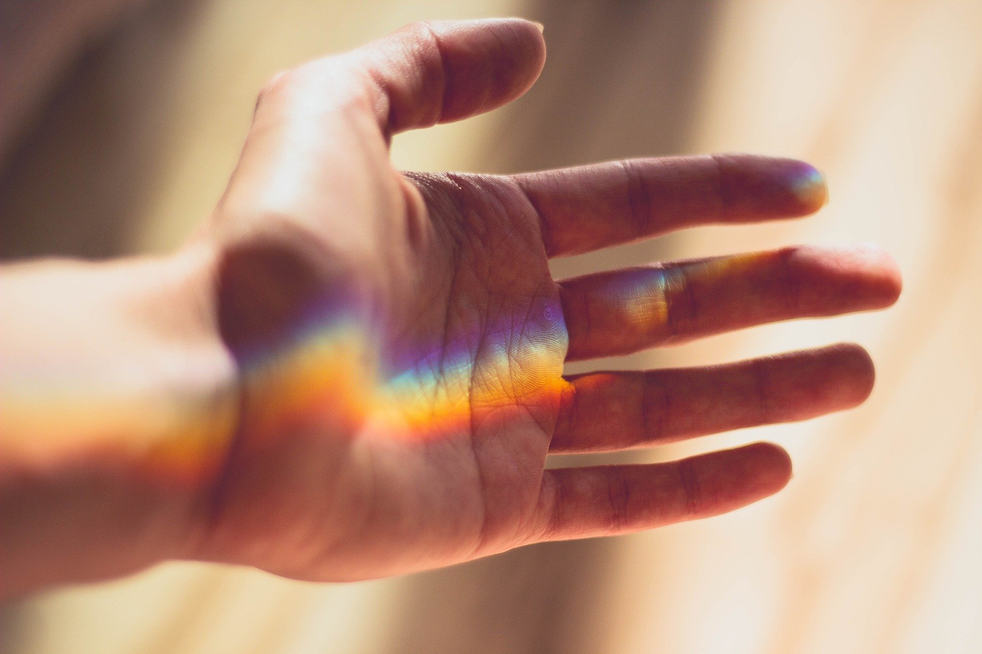 closeup of person's hand in beam of light, rainbow effect, anti-ageing for hands